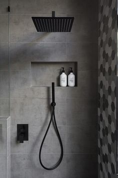 In this modern bathroom, the shower has a matte black rainfall shower head and a hand held shower head, as well as a tiled built-in shelf. - In this modern bathroom, the shower has a matte black rainfall shower head and a. Gray And White Bathroom, Grey Bathrooms, Master Bathrooms, Bathroom Accents, Bathroom Small, Grey Bathroom Tiles, Silver Bathroom, Master Baths, Luxury Bathrooms