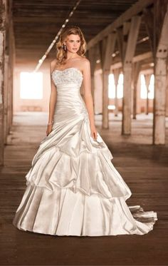 1324 Diamond Organza A-line Gown. Beaded bodice, ruched skirt and open back. Pickups in skirt add volume to this gown.