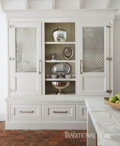 The center of a custom pantry, which is opposite the range wall, displays silver and mercury-glass pieces. Wire-grid doors backed with mercury glass conceal large serving dishes.  - Photo: Werner Straube / Design: Laura O'Brien