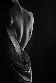 Low Key light creative portrait of woman's seductive back draped with an apparent sheet or large shirt.