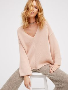 In an oversized silhouette, this heavy knit sweater features a V-neckline with cuffed wide sleeves. This easy style is the perfect pullover.