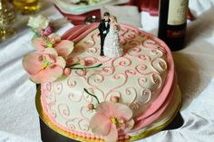 Unique Wedding Cake with white fondant and pink heart swirls and flowers with bride and groom on top