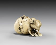 ANTIQUE CARVED IVORY NETSUKE: Two Chicks Antique carved ivory netsuke; of two chicks: one hatched, the other just hatching and movable within the cracked egg, inlaid eyes, signed, late 19th Century