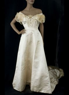 Satin Wedding Gown With Princess Line Seams, Deep Neckline Opening Is Trimmed With Swags Of Faux Pearls And Lace Flounces That Form Graceful Partial Sleeves (From The Commodore Perry Estate)   c.1908      (Front View)