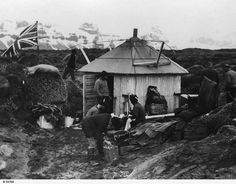 """GENERAL: The hut at Atlas Cove, Heard Island, used by members of the B.A.N.Z. Antarctic Research Expedition, 1929-31. Men are working outside and the Union Jack flag flies nearby. According to his daughter, Eric Douglas says on the back of his copy of the print """"Scientific party ashore at Heard Island - an old Norwegian Hut - Nov 1929""""."""