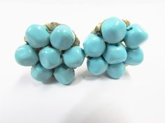 """Vintage Aqua Bead Cluster Clip On Earrings. These earrings feature a cluster of aqua colored plastic beads in a flower shape.  The beads are strung and glued into place on a gold tone metal setting.  The earrings are unmarked.  They are approx. 1"""".  The earrings are in good vintage condition.  You can see some of the old glue on the beads."""