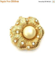 Brooch Sale Hattie Carnegie Floral Brooch Measures: Approx. 1 1/2 Mark: Hattie Carnegie in a cartouche Condition: Very Good vintage condition Unique stylized puffy flower brooch by Hattie Carnegie - Composed of heavy textured gold tone metal - Beautiful golden center faux pearl - Ice crystals scattered throughout the petals - Great dimension & texture in this pretty Carnegie pin Such a pretty piece ~ is it a flower or is it a shell it doesnt really matter because either ...