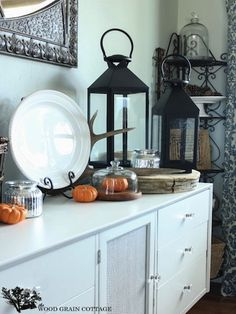 Oversized black lanterns and petite pumpkins evoke a Halloween vibe, while antlers—perched behind a plate stand—keep the look rustic.  We already have a lot of these elements.