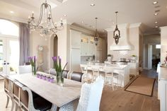 Just off the kitchen, the dining room is anchored by a whitewashed dining table and roll back chairs. The crystal chandelier adds a hint of glamor, while the centerpieces tie in the signature lavender hue found throughout the design.