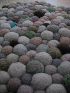 """Rug made from felted """"stones"""" sewn together. This one is handmade- I've seen these in upscale furniture stores lately. A great idea for disparate wool stashes, if I didn't have a cat. And two rabbits."""
