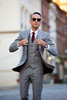The plaid three piece suit is a true gentleman's suit. Here's one way to wear it along with some tips how to style a grey plaid three piece suit.