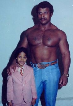 """shitloadsofwrestling: """"Rocky Johnson and Dwayne Johnson (The Rock) I was so excited to find this picture while scouring the webs for some old school photos. The Rock in that lilac-ass suit, and. The Rock Dwayne Johnson, Rock Johnson, Dwayne The Rock, Dwayne Johnson Young, Rare Historical Photos, We Will Rock You, Pink Suit, Professional Wrestling, Look At You"""