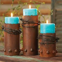 Rustic barbed wire is wrapped around the handmade recycled metal candle holders.