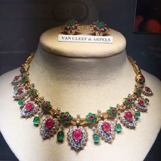 A magnificent ruby, emerald and diamond necklace of oriental inspiration, the double woven chain set with eight emerald and ruby flower motifs with cabochon emerald drop, suspending nine pear-shaped pendants, set with rubies and brilliant cut diamonds, mounted in platinum and 18 karat gold. Van Cleef & Arpels, Paris, circa 1960. At Epoque Fine Jewels