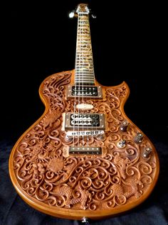 "Blueberry Hawk An intricately carved solid mahogany electric guitar with ""Hawk & Dragon"" motif hand carvings and fretboard inlays. Features high output Seymour Duncan pickups, bolt-on neck with an ebony reinforcement and combined mother of pearl and wood fretboard inlays. Price range $1,000"
