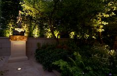 Up lighting the perimeter hedge adds a dramatic backdrop to a well lit gardening.
