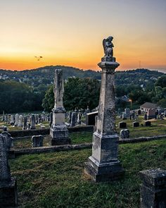 The sunsets on a hillside cemetery in Hermann Missouri with a angel atop a headstone praying.