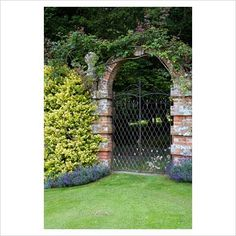 Classical ornate double caste iron garden gate through brick archway in high walled Victorian garden