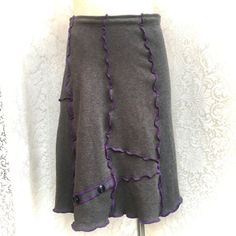 Upcycled Sweater Skirt, Medium to Large Women, Hand Crafted from Recycled Cotton Sweater, Patchwork in Grey with Purple Serged Seams, Button Accents  Pair it with boots, leggings, after ski wear, skinny jeans or whatever. Suitable for travel, work or play. Whatever youre doing, youll be making a great fashion statement. By recycling responsibly, people and the planet benefit in exponential ways:)  Waist: 32-38 with a one inch elastic waist Hips: 38: Length 22  Hand wash or gentle cycle/ lay…