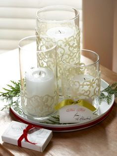 Winter Wonderland Candle Trio-  Give a one-of-a-kind Christmas gift with these beautifully adorned glass cylinders. Transform three plain cylinders into a snowfall-inspired trio with shimmery adhesive snowflakes (available at scrapbooking stores). Fit a pillar candle inside each cylinder, and include a ribbon-wrapped box of matches to complete the gift.