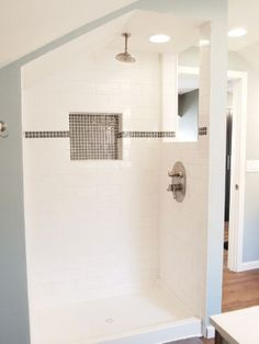 Spicing up white subway tile with glass tile accent strip and alcove
