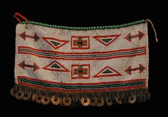 Kamba Beaded Apron Up until the beginning of the last century the wearing of goatskins by both men and women was widespread in rural Kenya. Over time fashions and materials evolved. What distinguished the diverse tribes was not so much the type of garment but the means of adornment, the colors chosen and the patterns employed. The Kamba were renowned for their wide and precisely patterned aprons dominated by small white beads. The use of chain and coins was widespread
