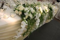 """The top table a spectacular """"Hanging Gardens of Babylon"""" design of Phalaenopsis Orchids, Roses, Peonies and Hydrangeas were literally flowing from the table"""