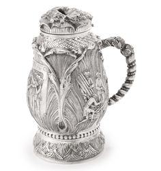 "The Michael & Judy Steinhardt Judaica Collection - A CONTINENTAL SILVER TANKARD-FORM CHARITY BOX FOR A BURIAL SOCIETY foliate bud form, chased with scenes of burial, spiraled handle and flower-form cover, Hebrew inscription ""charity saves from death."" apparently unmarked, height 8 3/4 in. 20th Century"