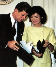 Jackie and Jack Kennedy They are looking at the First White House guidebooks for the tourists that come to the White House. They sold for $.1.00.