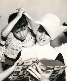 """From the Daughters of Charity Province of St. Louise Archives Facebook page, (Image used with permission of the Daughters of Charity Provincial Archives)  """"A picture so cute we just had to share it - this youngster makes sure to get a 'bird's eye view' as Sister reads a story. Hope it brightens your day as much as it brightened ours!""""  (Photo property of the Archives.)  Visit the Archives Facebook page at: https://www.facebook.com/#!/dcarchives"""