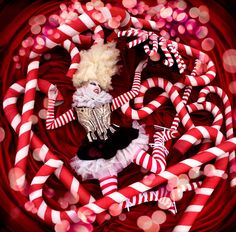 Vortex - Costume made by me  Candy cane props made and designed by me (with the help of some friends)  This was shot from the top of a ladder with the model surrounded by a huge spiral of over 20 meters of red fabric. All the candy canes are real and were balanced in this position, nothing was cloned or added in post. The coloured light bubbles were created as a layer afterwards to add a little magic effect, something I don't usually do but it felt right for this picture.  Wonderland be...