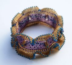 My latest progression from Contemporary Geometric Beadwork by Kate McKinnon. This is my winged and horned bangle in shades of what. Seed Bead Bracelets, Seed Bead Jewelry, Beaded Jewelry, Seed Beads, Bracelet Designs, Bead Art, Bead Weaving, Beading Patterns, Making Ideas