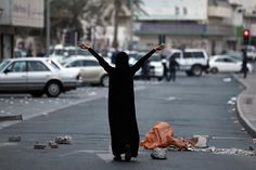 May 16, 2012 An anti-government protester walks towards riot police, holding stones in her hands, during a protest asking for the release of human rights activists in the village of Sanabis west of Manama, Bahrain. Hamad I Mohammed/Reuters