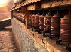 PRAYER WHEELS AT DUSK MUSTANG REGION, ANNAPURNA RANGE, NEPAL. Spinning prayer wheels are illuminated on a cliffside monastery in the high country of Nepal.
