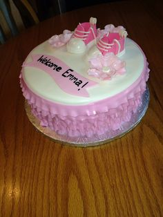 Pink baby shower cake with handmade booties.