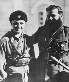 "The caption of this press photograph read, ""Greek Fighter Born in U.D.: Aris Velouchiotis (right), Greek Andartie leader, is shown with one of his aides, 15-year-old Louis Petropoulagos,  The photograph was taken November 16, 1944 after the Germans had evacuated the Balkans, but the confrontatiin with theBritish and Royal Government was shaping up."