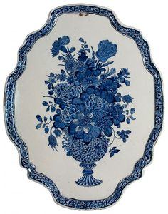 18th Century Faience Delft Blue Plaque - Delft, Netherlands| The plaque has a molded rim decorated with a floral motif. Depicted is a richly filled flower vase. Perforated in order to be able to be hung. -- Van Nie Antiquairs