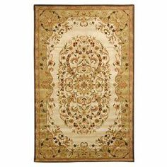 """Stylishly anchor your living room or master suite with this hand-tufted wool rug, featuring a Persian-inspired floral motif.    Product: RugConstruction Material: WoolColor: Beige and greenFeatures:  Durable cotton canvas backing0.625"""" Pile height Note: Please be aware that actual colors may vary from those shown on your screen. Accent rugs may also not show the entire pattern that the corresponding area rugs have.Cleaning and Care: Professional cleaning recommended"""