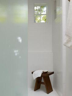 The shower is tiled in Avalon II matte white tile with a Thassos Mosaic white marble tiled floors, both from Ann Sacks.
