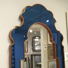 The Sapphire Mirror from designer Bunny Williams has a shimmering blue glass finish accented with a gold-speckle frame.