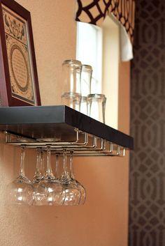 DIY floating shelf wine rack. Rack and shelf both from Lowes. Screw two racks on the underside of shelf, then hang shelf. Easy.