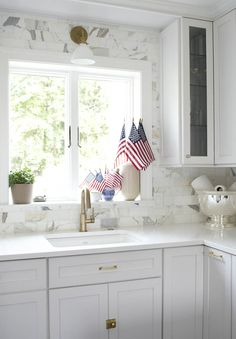 Brass accents and hardware in a beautifully styled white kitchen.