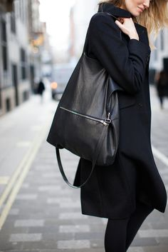 A simple, black leather tote carries (and hides) a multitude of sins. This COS style is one of the best we've seen.