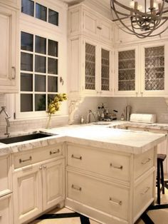 This elegant kitchen has marble countertops, cream colored cabinets, a unique light fixture, and glass cabinet doors.
