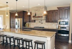 Knotty alder cabinets, venetian gold light granite, stainless appliances, stone hood vent with rustic wood mantle