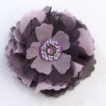 """Esther Flower  (#1474)  $8.95  Vi Bella Jewelry - With a hint of vintage nostalgia, the Esther Flower is made up of frayed fabric in multiple hues of purple and finished off with an intricately beaded centerpiece. Can be worn as a pin or a clip. Width: 3"""" Handmade in Haiti."""