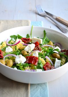 pastasalade met rucola, groene olijven, rode ui, zongedroogde tomaat en eventueel feta of zachte geitenkaas of pijnboompitten