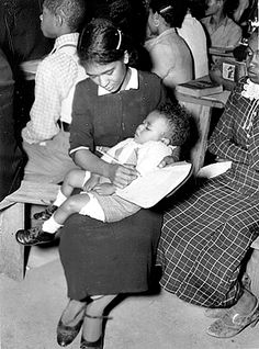 """This woman in Lafayette Parish could not leave her infant son at home alone, so she brings him along, reaching over the sleeping child to practice her writing."" (New Deal outreach, 1930s)"