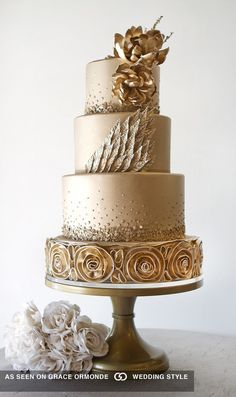 Gold four-tier cake featuring gilded leaves, florals and rosettes.