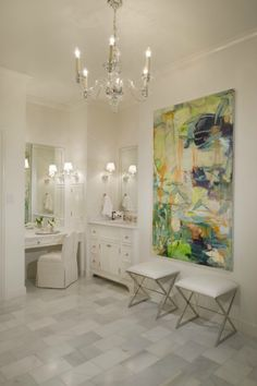 Master bathroom with Visual Comfort Lighting George II Chandelier, abstract canvas art, polished nickel x-base ottomans, built-in vanity with marble countertop and white single bathroom vanity.